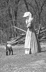A farmer from 1850 style simulated park with a newborn lamb.