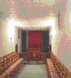 Chairs line the wall, and a simple altar lies at one end, and a doorway behind tha.  In an adjacent room near the viewer in this photo, is a kitchen.